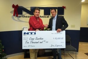 NTI President Jim Liponis (left), presents a donation of $10,000 to Michael Smith of Camp Sunshine